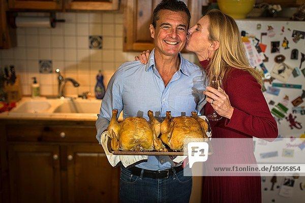 Porträt eines reifen Paares mit Brathähnchen in der Küche