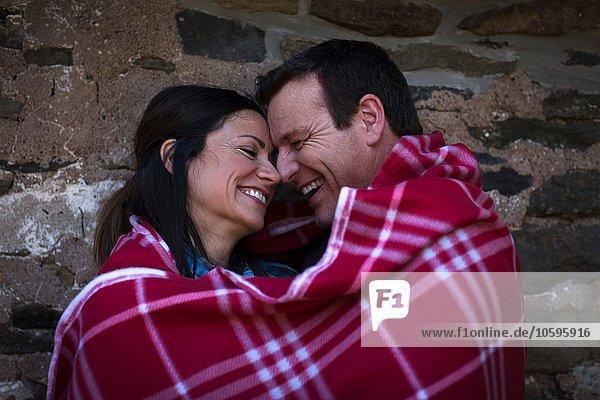 Fröhliches  romantisches  reifes Paar  nachts in eine Decke gehüllt.
