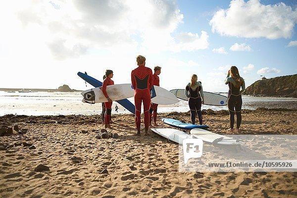 Surfergruppe am Strand stehend  Surfbretter haltend  Rückansicht