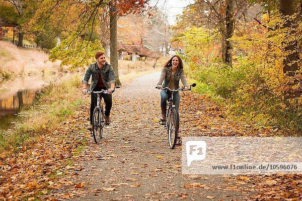 Glückliches junges Paar beim Radfahren am Flussufer im Herbst