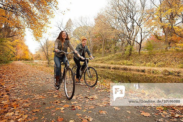 Glückliches junges Paar  das im Herbst am Flussufer entlang radelt