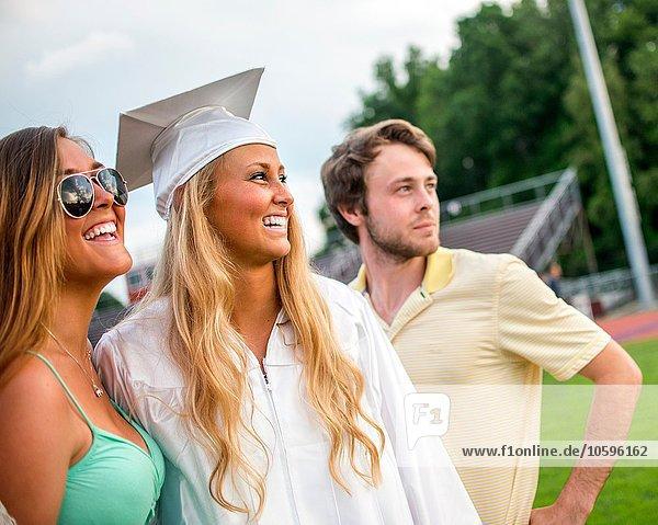 Junge Absolventin mit Schwester und Bruder bei der Abschlussfeier