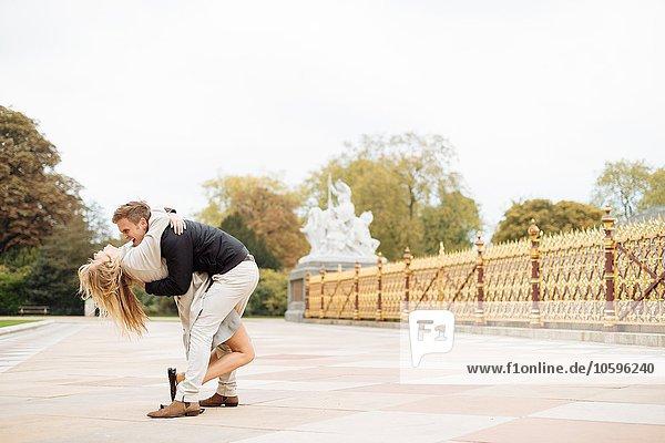 Romantisches junges Paar  das sich beim Umarmen bückt.