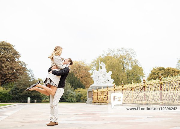Romantischer junger Mann hebt Freundin im Park auf
