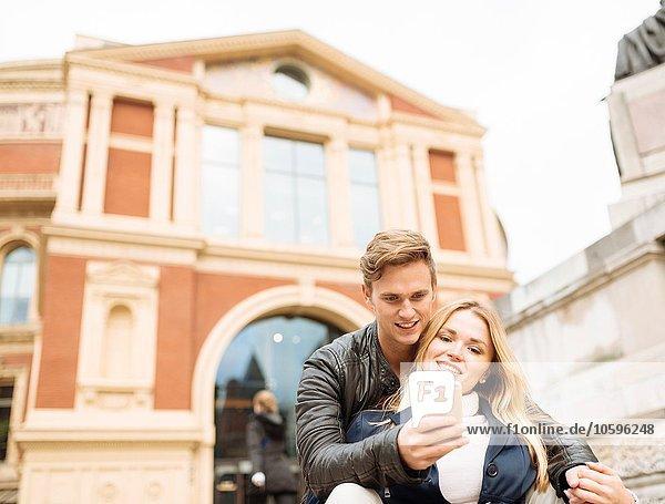 Young couple taking smartphone selfie outside Albert Hall  London  England  UK