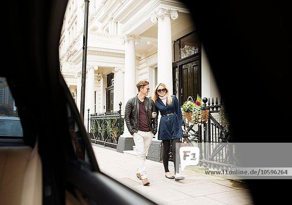 Autofensteransicht des jungen Paares  das auf der Straße spazieren geht  London  England  UK
