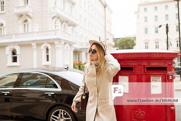 Stylish young woman next to red post box  London  England  UK