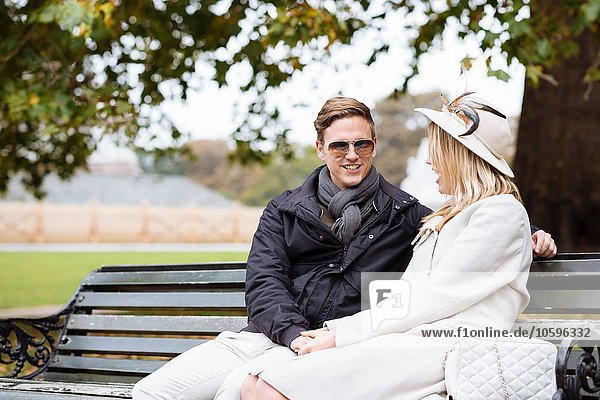 Young couple sitting on park bench  London  England  UK