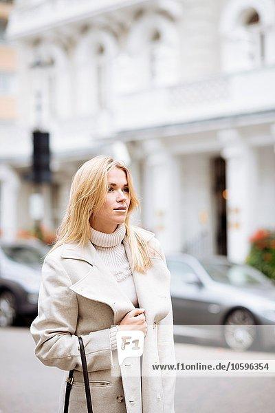 Stilvolle junge Frau wartet auf der Straße  London  England  UK Stilvolle junge Frau wartet auf der Straße, London, England, UK