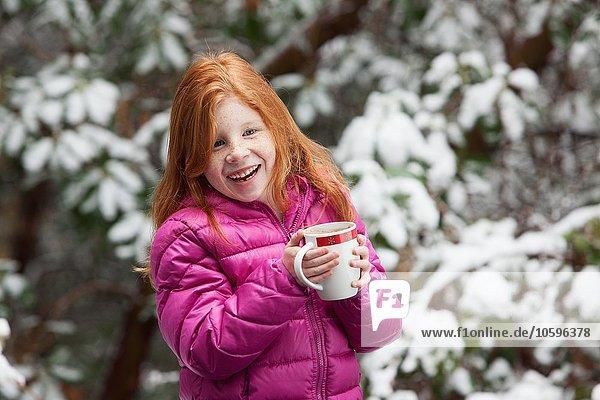 Rothaariges Mädchen vor schneebedeckten Bäumen  mit rosa gepolstertem Mantel  der den Becher hält und lächelnd wegsieht.