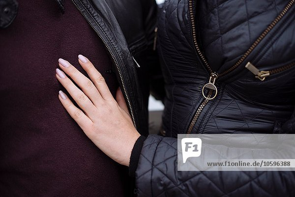 Cropped close up of young womans hand on boyfriends chest