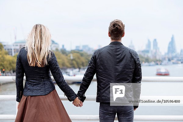 Rückansicht eines romantischen jungen Paares vor der Themse  London  England  UK