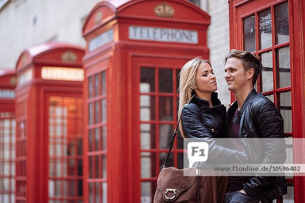 Romantic young couple next to red phone boxes  London  England  UK