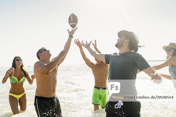Männliche und weibliche erwachsene Freunde spielen American Football im Meer in Newport Beach  Kalifornien  USA