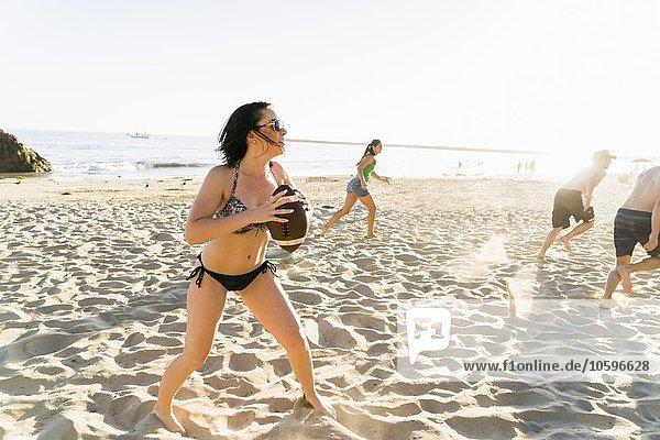 Männliche und weibliche erwachsene Freunde spielen American Football am Newport Beach  Kalifornien  USA