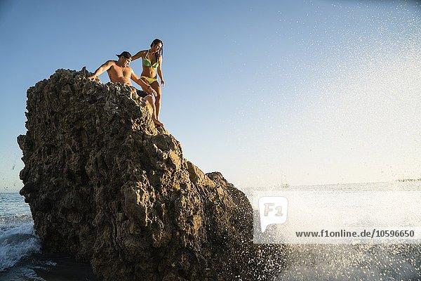 Junges Paar auf Felsen mit Wellen am Newport Beach  Kalifornien  USA