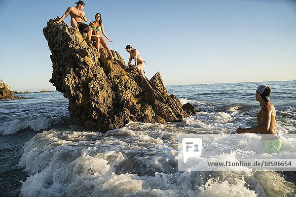 Erwachsene Freunde beim Waten und Klettern auf Felsformationen in Newport Beach  Kalifornien  USA