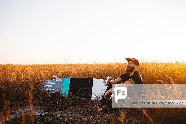 Männlicher Surfer trinkt Bier im Feld des langen Grases bei Sonnenuntergang  San Luis Obispo  Kalifornien  USA