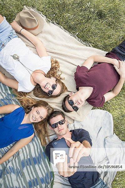 Gruppe junger Erwachsener auf Picknickdecken liegend  Selbstporträt mit dem Smartphone aufnehmend Gruppe junger Erwachsener auf Picknickdecken liegend, Selbstporträt mit dem Smartphone aufnehmend