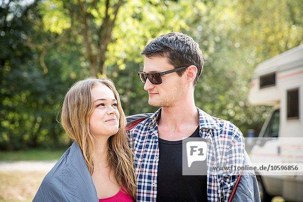 Junges Paar in Decke gewickelt  im Freien  von Angesicht zu Angesicht  lächelnd