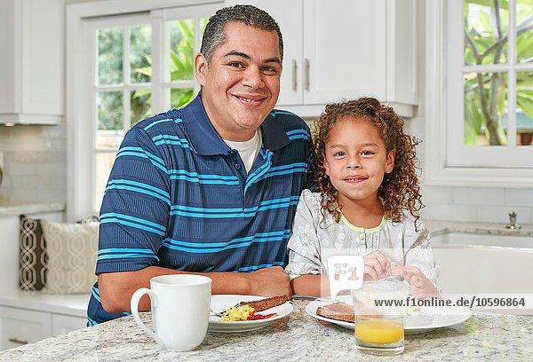 Vater und Tochter Seite an Seite an der Küchentheke beim Frühstücken  Blick auf die Kamera lächelnd
