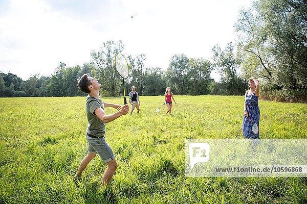 Gruppe junger Erwachsener beim Badmintonspiel im Feld