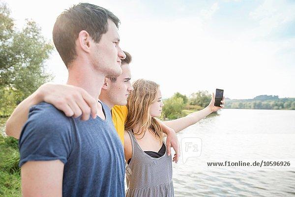 Drei junge Erwachsene beim Selbstporträt  mit dem Smartphone  im Freien Drei junge Erwachsene beim Selbstporträt, mit dem Smartphone, im Freien