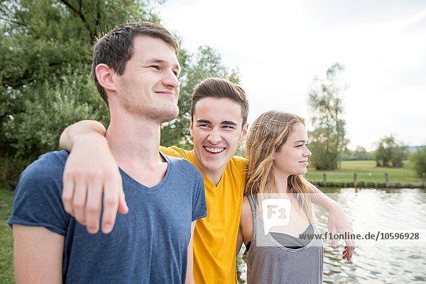 Gruppe junger Erwachsener  am See stehend  lächelnd Gruppe junger Erwachsener, am See stehend, lächelnd