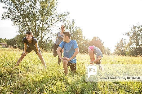 Gruppe von Freunden  die im Feld trainieren Gruppe von Freunden, die im Feld trainieren