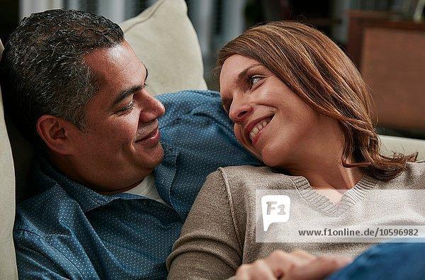 Kopf und Schultern des Paares kuscheln sich auf dem Sofa von Angesicht zu Angesicht lächelnd.