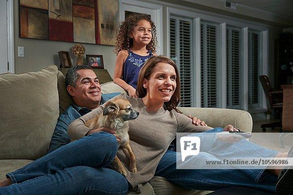 Eltern und Mädchen im Wohnzimmer auf dem Sofa mit einem Hund  der lächelnd wegguckt.