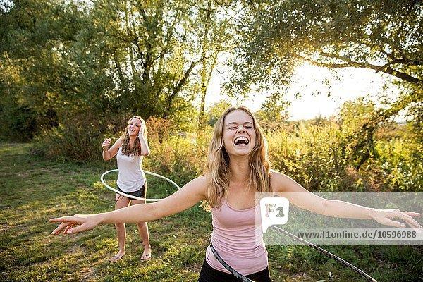 Zwei junge Mädchen in ländlicher Umgebung  die mit Hula-Reifen herumalbern Zwei junge Mädchen in ländlicher Umgebung, die mit Hula-Reifen herumalbern,