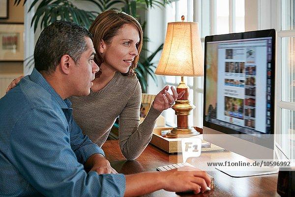 Seitenansicht des Paares am Schreibtisch mit Computer