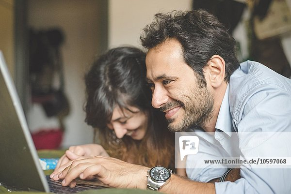 Kopf und Schultern des jungen Paares liegend auf der Vorderseite mit Laptop-Computer