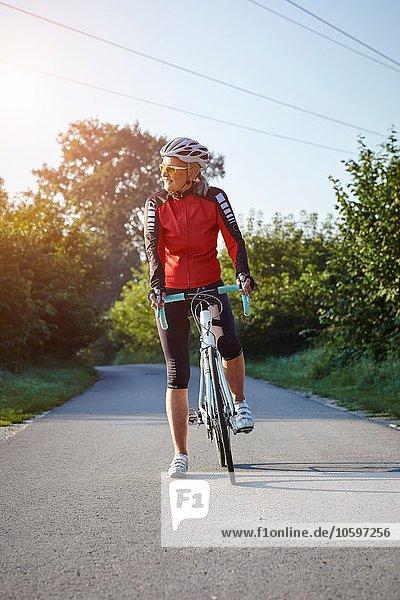 Reife Radlerin mit Fahrrad auf der Landstraße