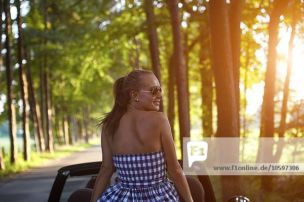 Young woman in back seat of convertible car on rural road