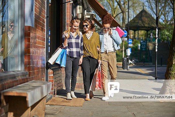 Frau tragen lächeln gehen Tasche Straße frontal kaufen Ansicht Seitenansicht