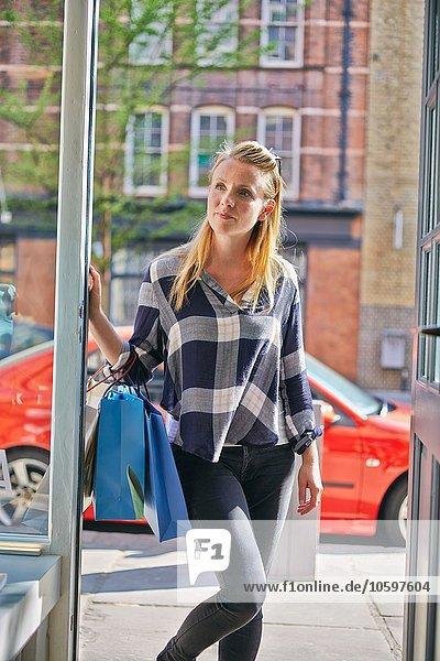 stehend Frau sehen Eingang Tasche halten kaufen Mittelpunkt wegsehen Reise Erwachsener