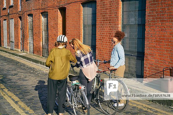 Kopfsteinpflaster stehend Städtisches Motiv Städtische Motive Straßenszene Frau halten Fernverkehrsstraße Rückansicht Ansicht Fahrrad Rad Zimmer