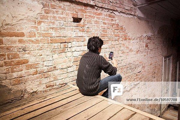 Mittlerer Erwachsener Mann  der mit dem Smartphone auf der Treppe sitzt  Rückansicht