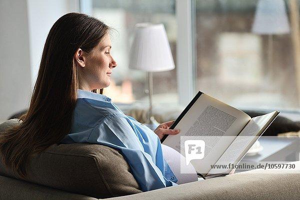 Schwangere sitzend auf dem Sofa  Lesebuch