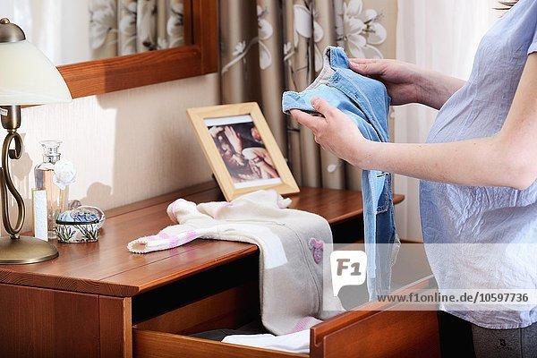 Schwangere Frau mit Babykleidung  Mittelteil Schwangere Frau mit Babykleidung, Mittelteil