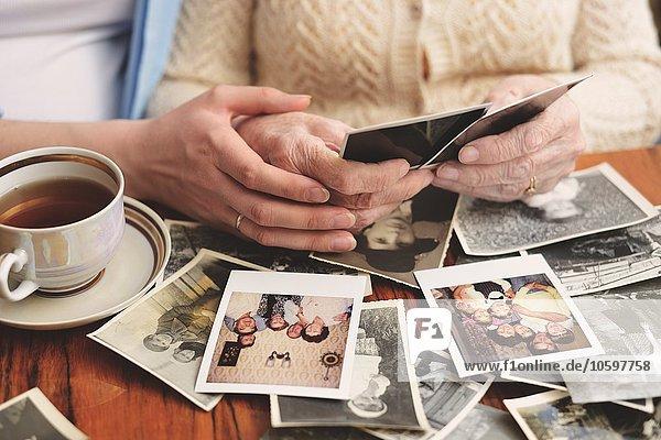 Seniorin und Enkelin am Tisch sitzend  Blick durch alte Fotos  Mittelteil