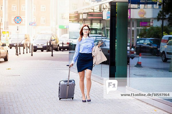 Businesswoman with wheeled suitcase  Warsaw  Poland