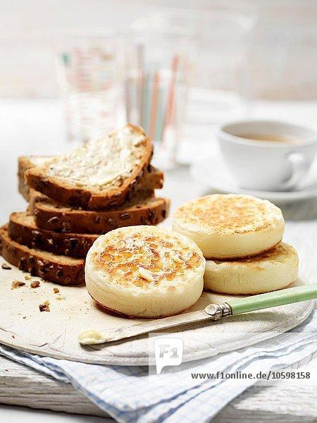 Crumpets und entkerntes Vollkornbrot mit Butter auf Vintage-Schneidebrett mit Tasse Tee