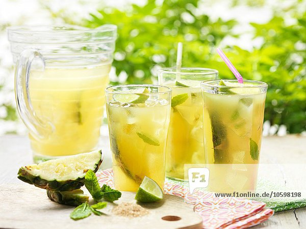 Gläser hausgemachter goldener Rumpunsch mit Limette  Ananas  Minze und Eis