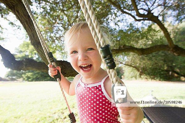 Portrait of female toddler on tree swing