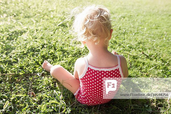 Rear view of female toddler wearing red spotted bathing costume sitting on grass