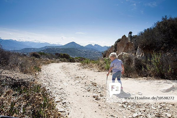 Female toddler on dirt track with walking stick  Calvi  Corsica  France