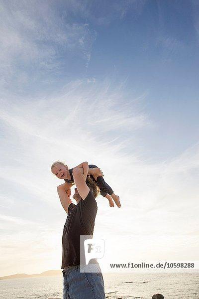 Mature man lifting up his toddler daughter on beach  Calvi  Corsica  France